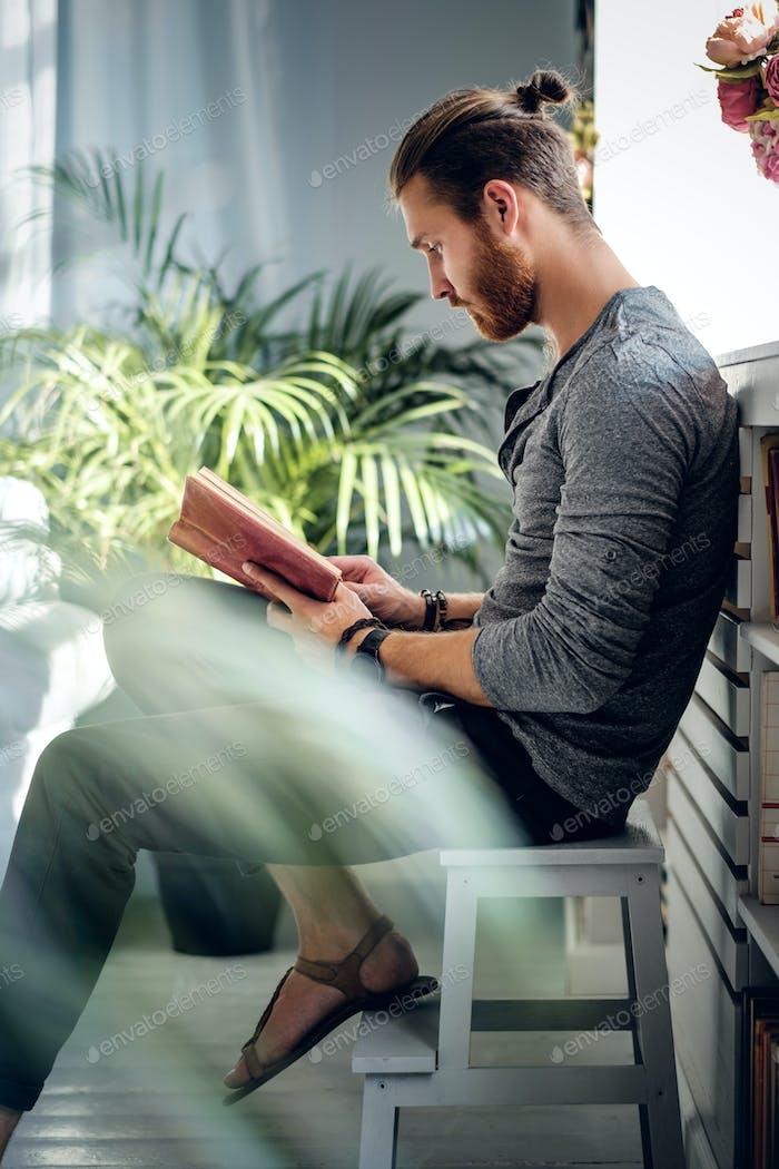 Un hombre leyendo un libro.