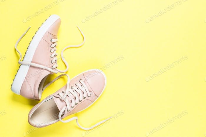 Woman fashion pink shoes on yellow background.