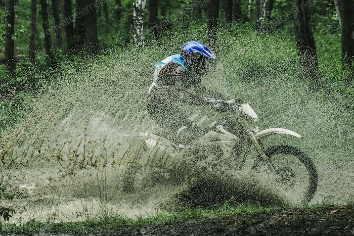 Motocross bike crossing creek, water splashing