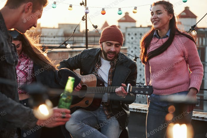 Guitarist sits and singing for his friends at the rooftop with decorative colored light bulbs