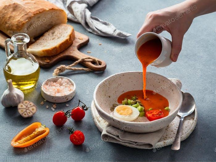 Handgießen von Gaspacho Suppe