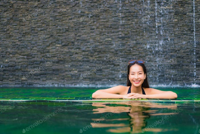Portrait beautiful young asian woman in swimming pool around hot