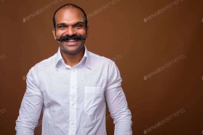 Portrait of happy Indian businessman with mustache in casual clothing