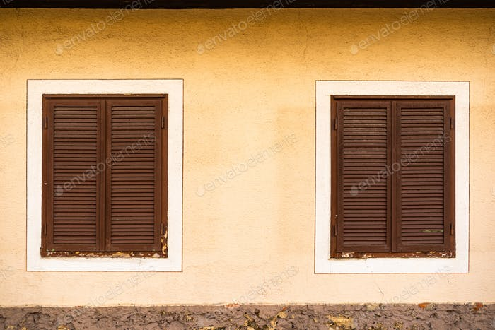 Two wooden windows with brown shutters on Austrian house