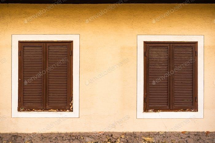 Zwei Holzfenster mit braunen Fensterläden auf österreichischem Haus