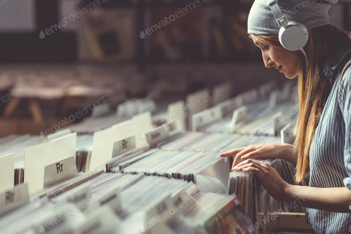 Young girl with headphones browsing vinyl records