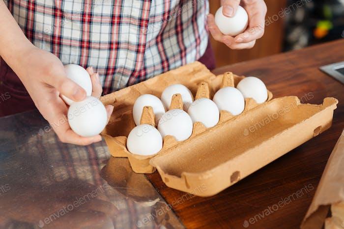 Frische Eier von den Händen der jungen Frau in der Küche