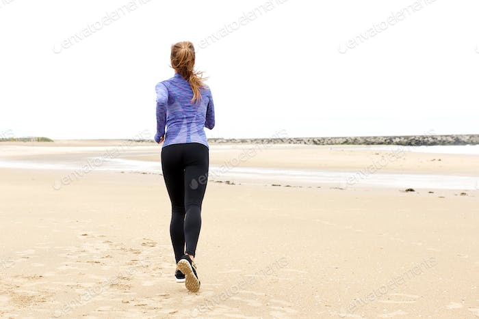 Athletic woman running on beach by sea