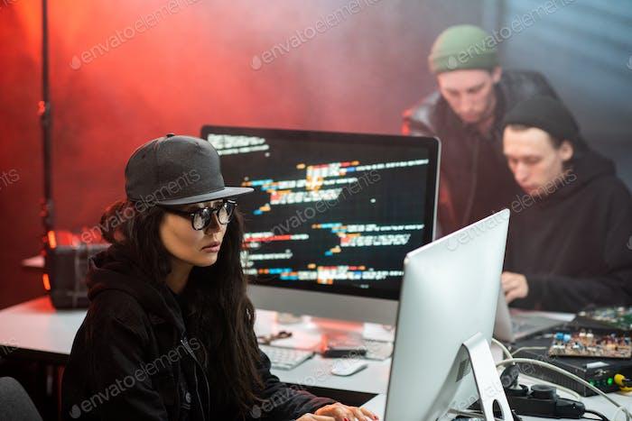Joven asiática en traje de hacker decodificación información