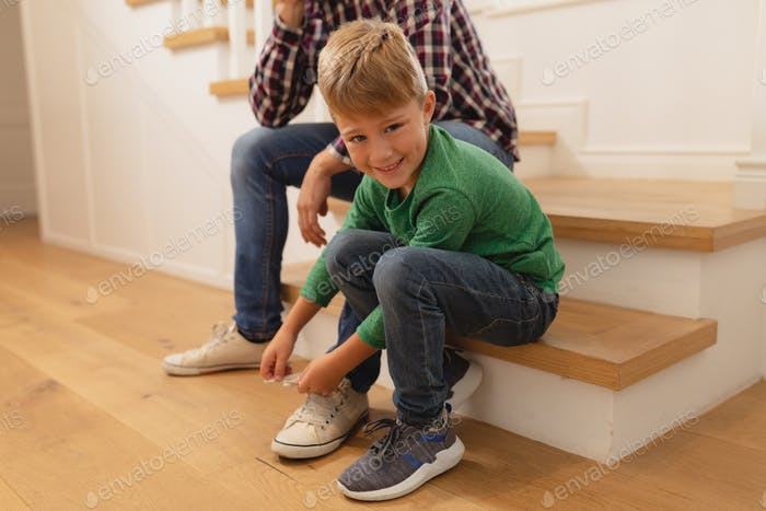 Front view of happy Caucasian son tying his father shoelaces in a comfortable home