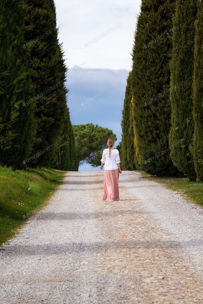 Woman walking among high cypress trees