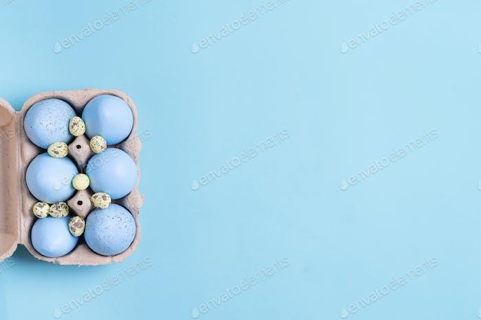 Festlicher Osterrahmen aus Papierbox mit handgefertigten blau bemalten Eiern auf einem blauen Hintergrund
