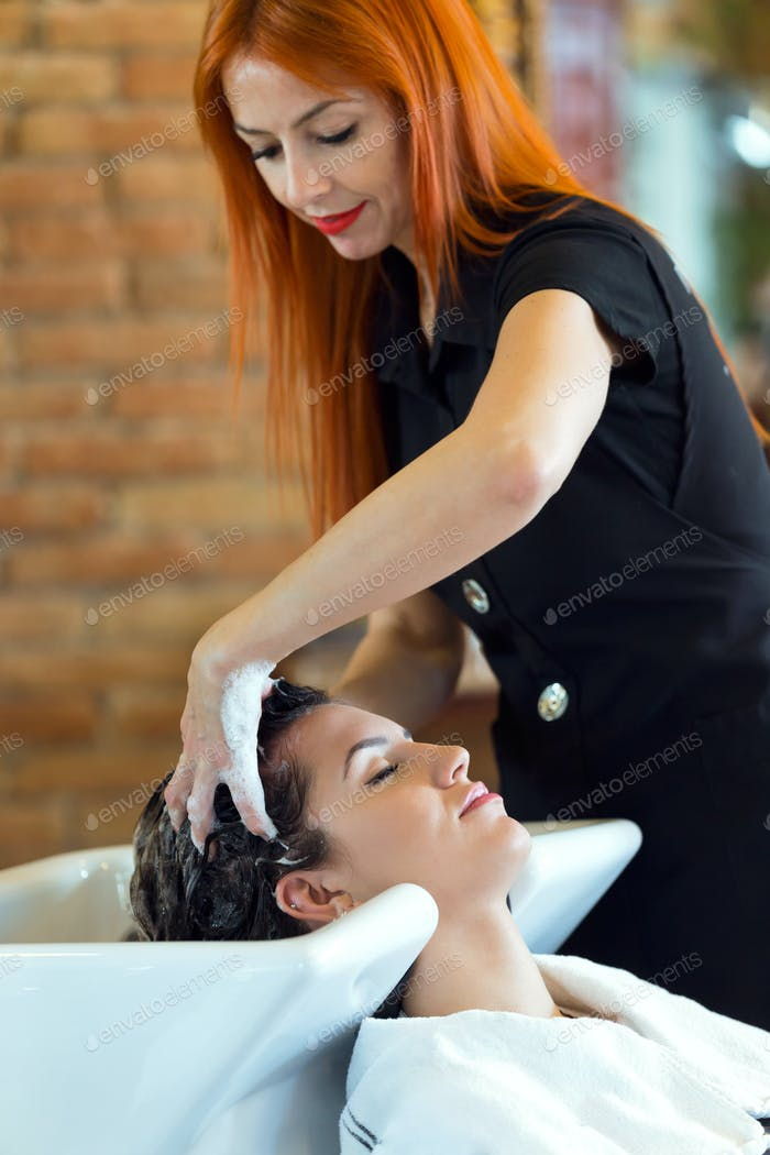 Beautiful young woman washes hair in a beauty salon.