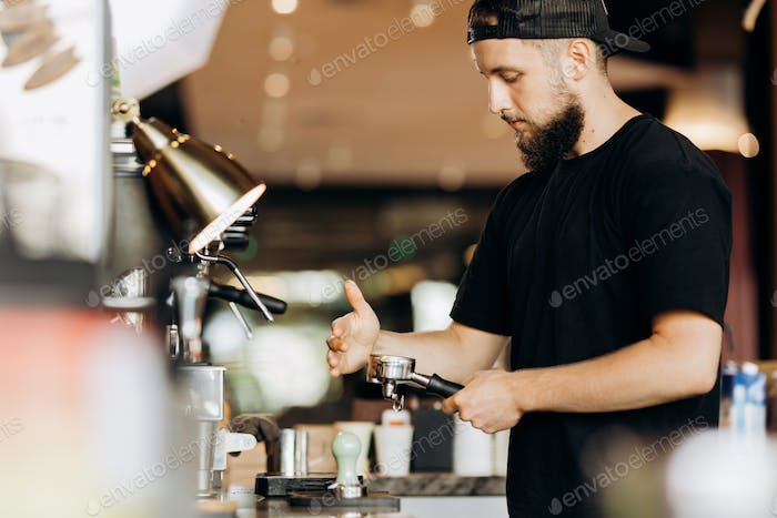 A stylish young man with beard,wearing casual clothes,cooks coffee in a coffee machine in a modern
