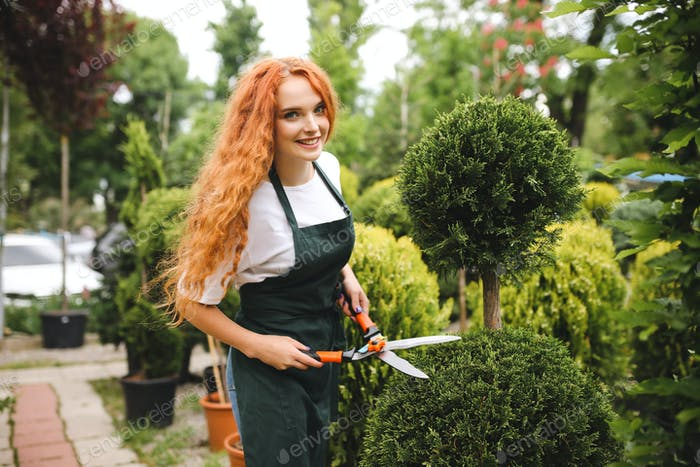 Smiling lady gardener with redhead curly hair standing in apron and holding big garden scissors