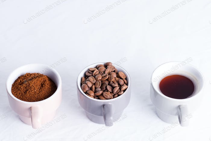 Three cups of different condition of coffee - beans, freshly ground and coffee drink on a marble