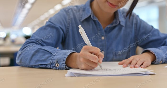 Woman do her essay at library