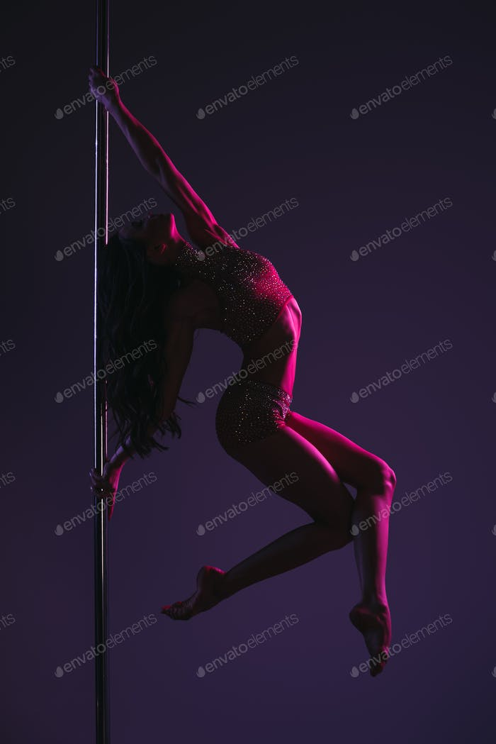 side view of athletic flexible girl exercising with pole on blue