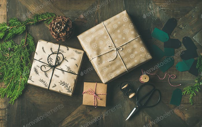 Flat-lay of gift boxes, rope, fur branches, scissors, cones, stickers