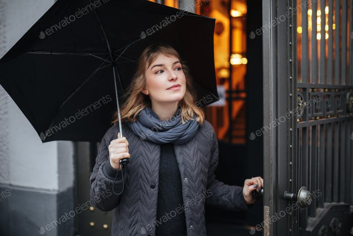 Portrait of pretty lady standing on street with black umbrella and looking aside isolated