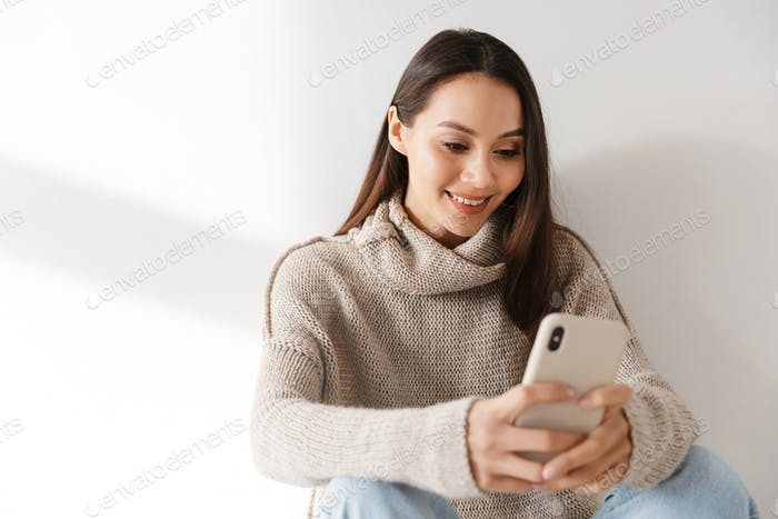 Image of smiling asian woman sitting and using smartphone