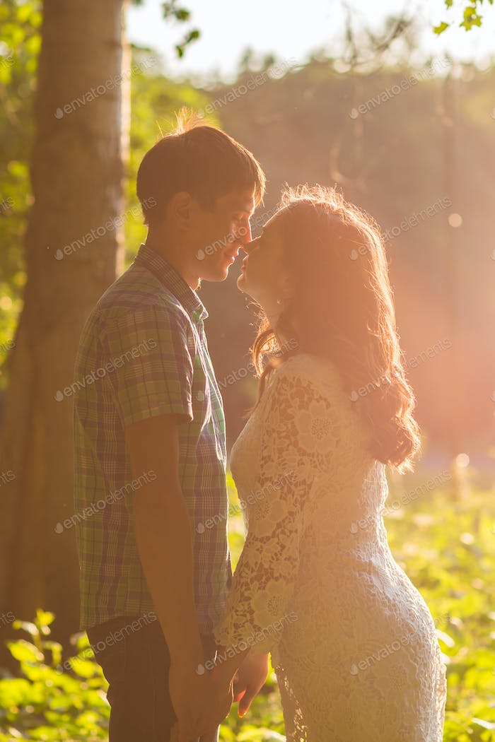 Young attractive couple in love kissing in summer nature