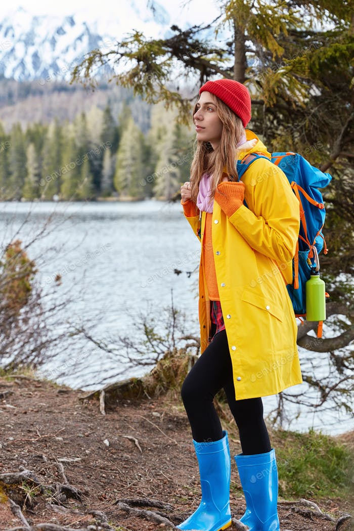 Photo of thoughtful young woman stands in full length, wears red headgear, yellow raincoat, looks in