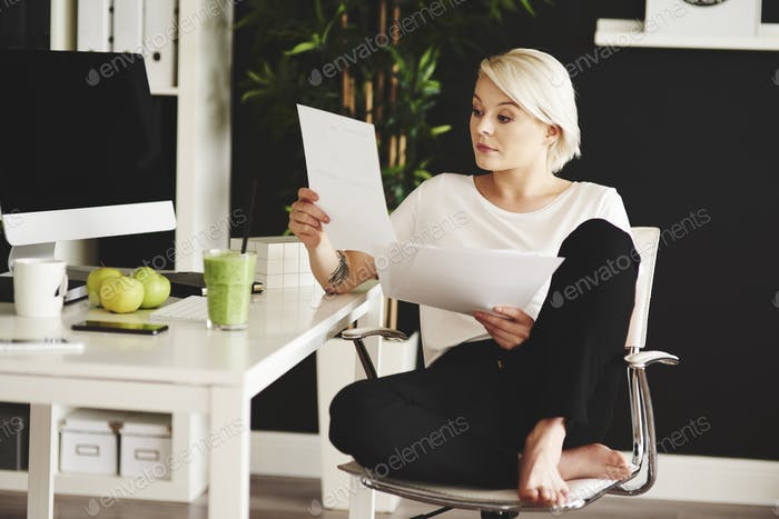 Barefoot freelancer reading documents at home office