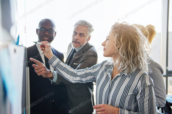 Corporate colleagues strategizing together on a whiteboard in an office