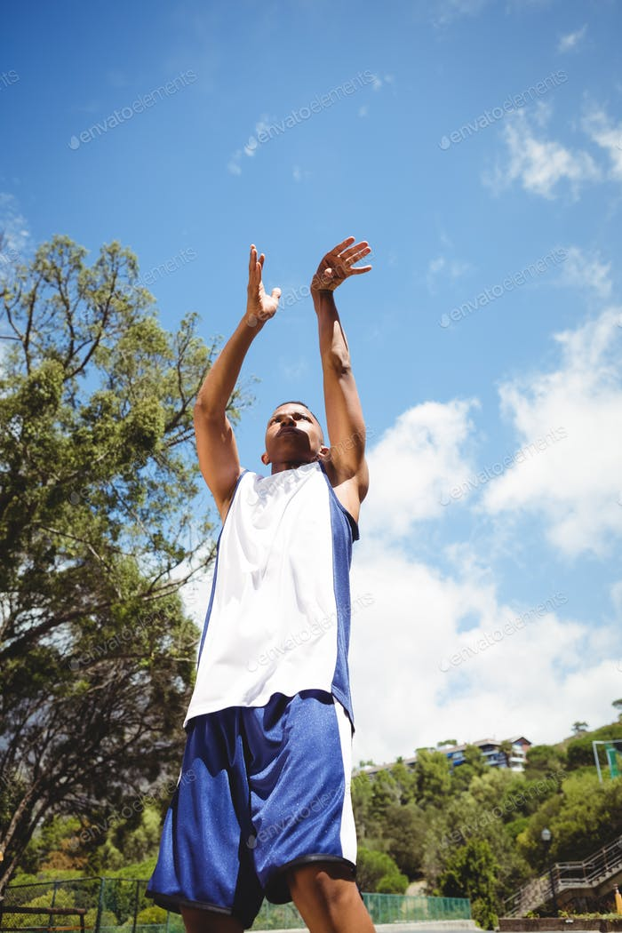 Low angle view of male teenager practicing basketball