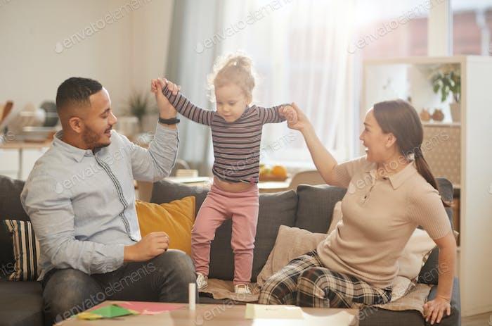 glücklich Familie spielen mit Niedlich kleine Tochter zu Hause