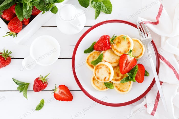 Cheese pancakes, fritters or syrniki with fresh strawberry and yogurt. Healthy and tasty breakfast