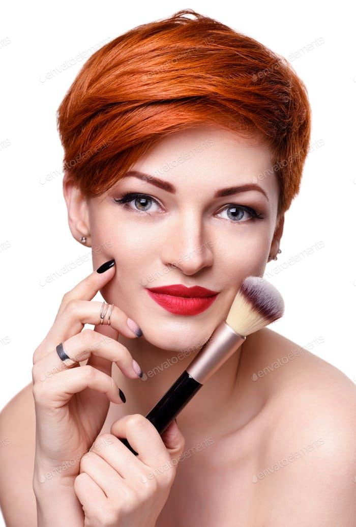 Portrait of a beautiful young woman with short red hair with a makeup brush