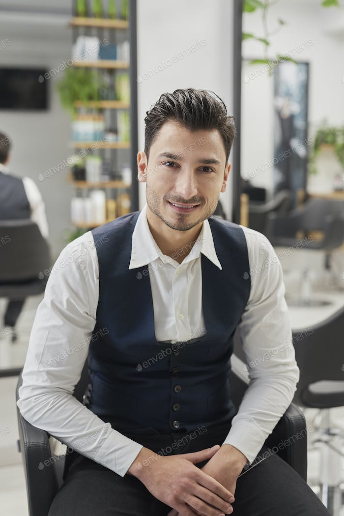 Portrait of smiling male customer sitting in hair salon