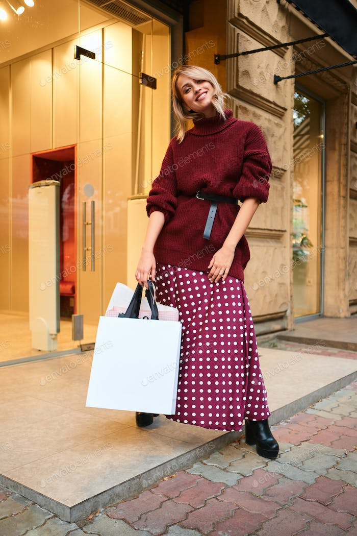 Smiling stylish blond girl with shopping bags joyfully looking in camera after shopping outdoor