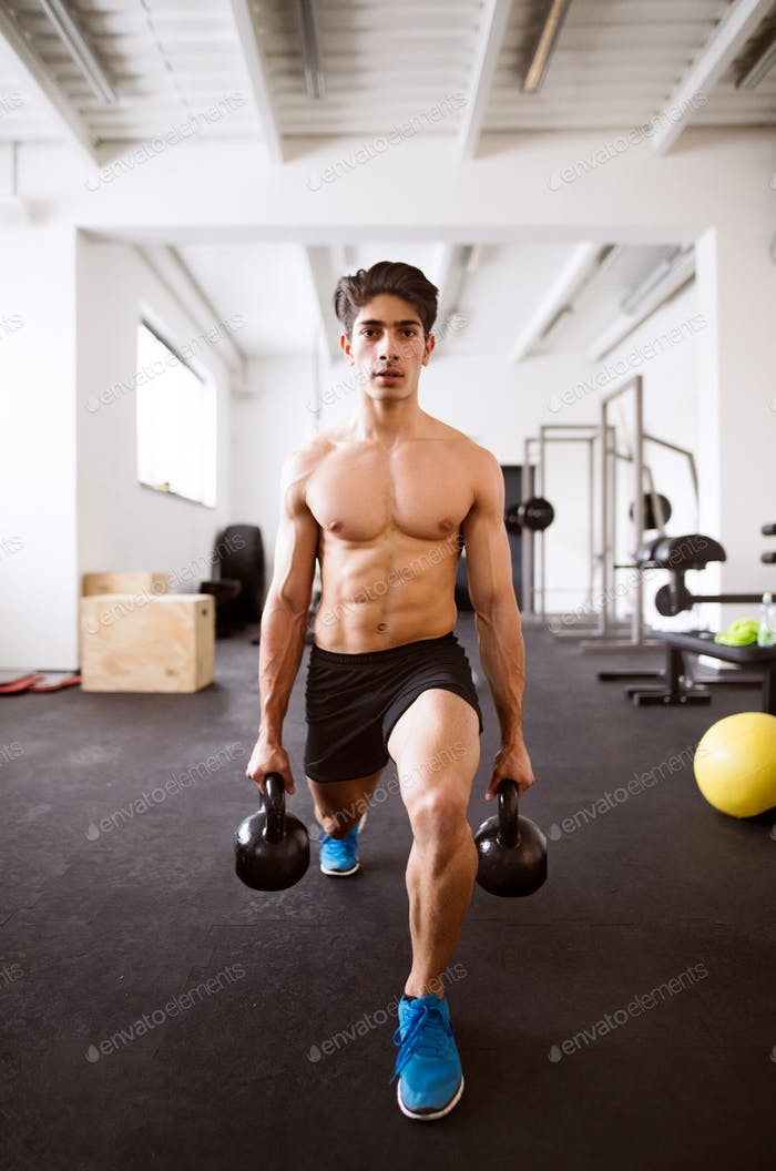 Young fit hispanic man in gym doing lunges with kettlebells