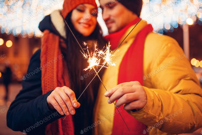 Winter evening, love couple with sparklers outdoor