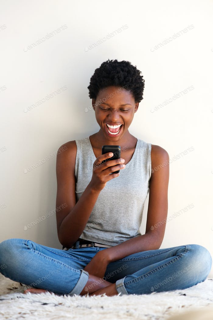 happy young black woman using cellphone and laughing
