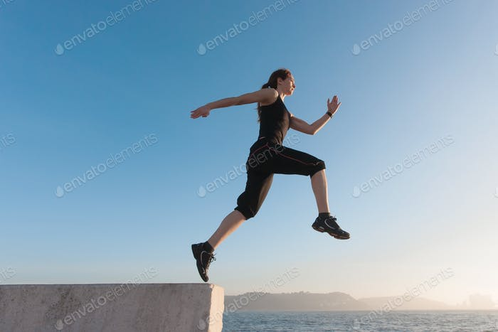 Fit women jumping with blue sky in background