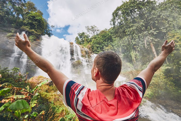 Happy traveler near waterfall