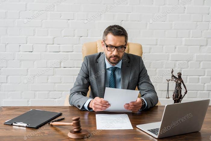 juez masculino serio que trabaja con los papeles y el ordenador portátil en el cargo