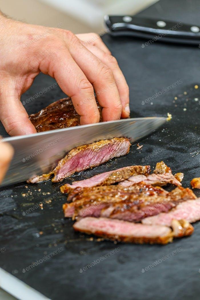Cook is slicing grilled pork steak