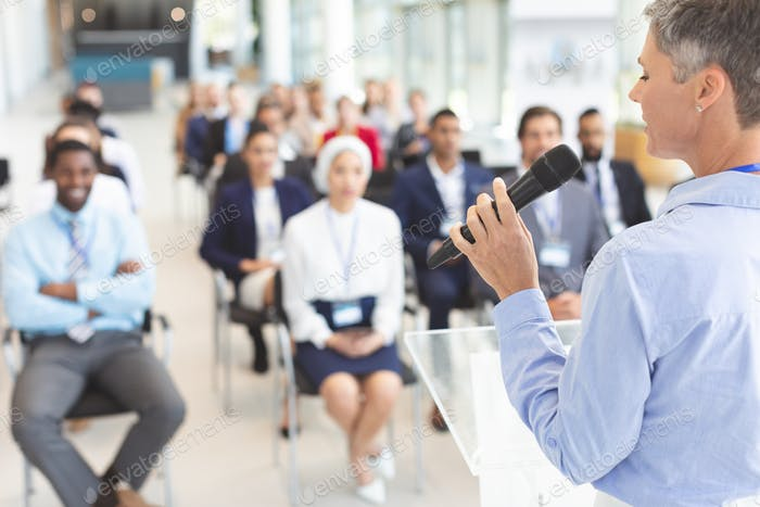 Female speaker speaks with microphone to business people in a business seminar in a conference room