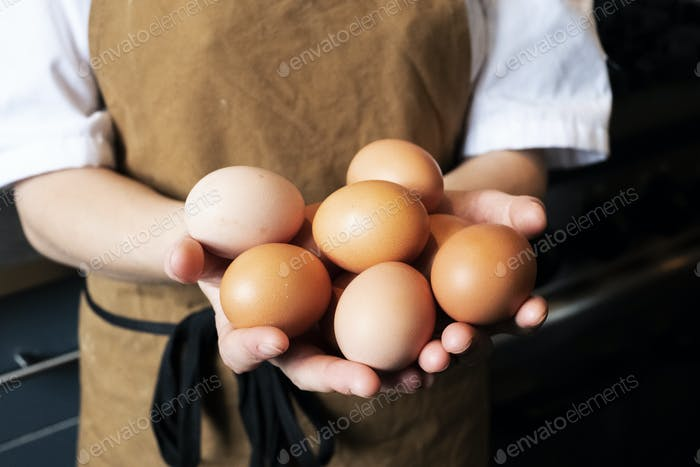 High angle close up of person wearing apron holding fresh brown eggs.