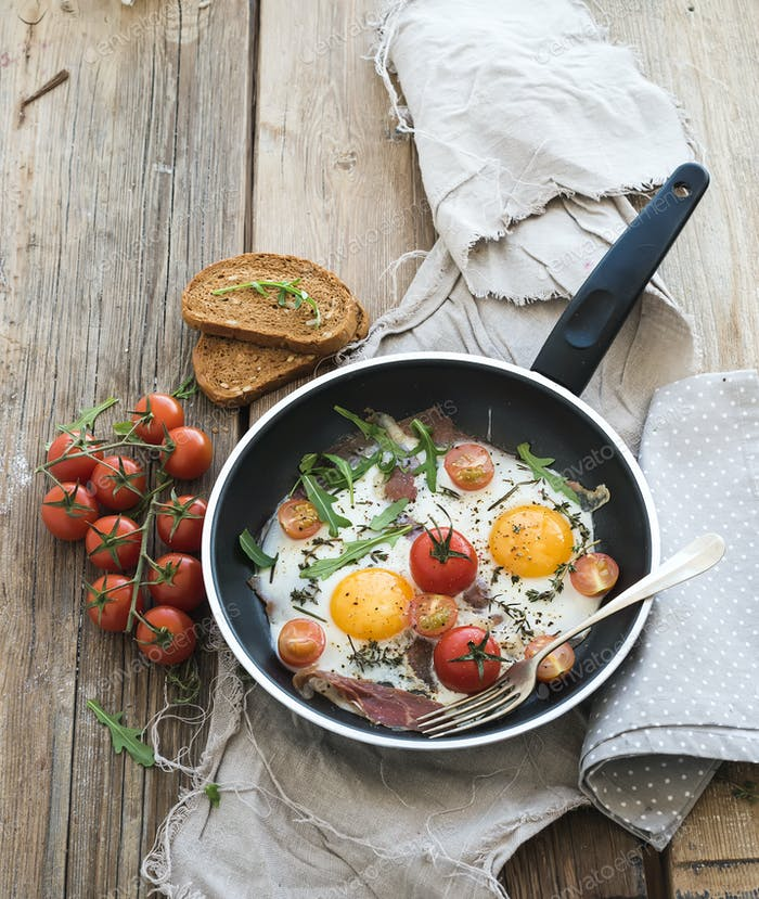 Pan of fried eggs, bacon and cherry-tomatoes with bread on rustic wood table surface