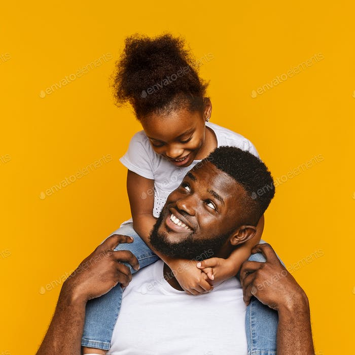 Cute african american little girl sitting on her daddy's shoulders
