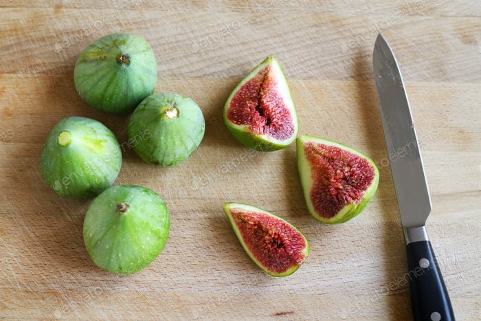 Figs and knife on wooden chopping board