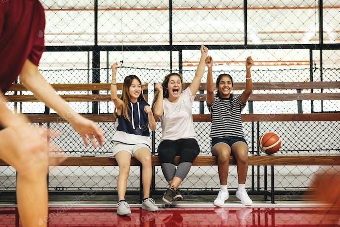 Teenage girls cheering the boys playing basketball