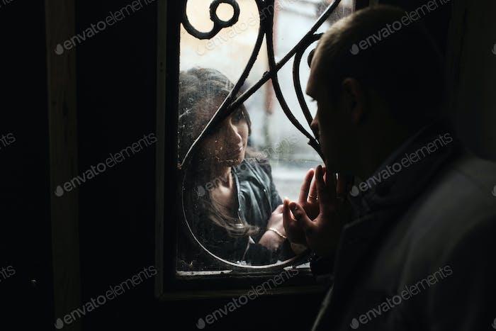 Europäisches junges Paar, das sich gegenseitig durch das Fenster anschaut