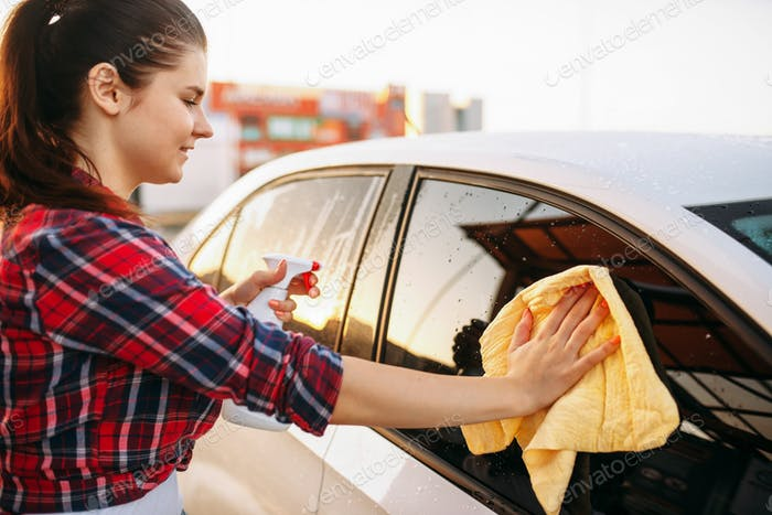 Woman cleans front glass of the car with spray